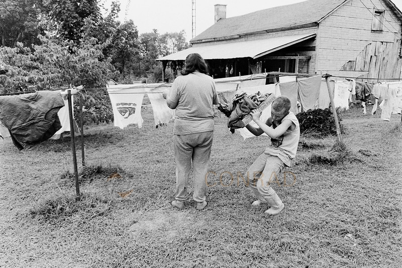 Daily Chores - Nellie Cardwell, left, is helped by her grandson Allen while trying to finish the laundry. (© Paul Conrad/Paul Conrad Photography)