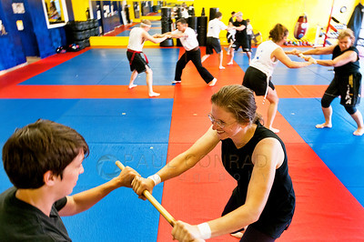 © Paul Conrad/Pablo Conrad Photography - Black belt Anna Haskin, left, and Julia Marting, both from Bellingham, practice stance and balance during Escrima Filipino Stick Fighting technigues during the PNW Muay Thai camps at Total Confidence Martial Arts in Bellingham, Wash.