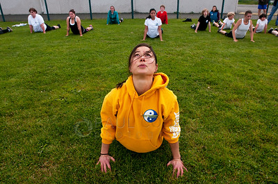 © Paul Conrad/Pablo Conrad Photography Total Confidence Martial Arts owner/instructor Katherine Holmes leads the group in stretching exercises during the black belt qualifier at Bellingham High School on Saturday morning June 9, 2012, in Bellingham, Wash.