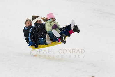 @ Paul Conrad/Pablo Conrad Photography Three girls hang on for dear life as they soar through the air while sledding on Buttermilk Mountain near Aspen, Colo.