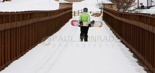 © Paul Conrad/Pablo Conrad Photography After a long day of riding at Buttermilk, a snowboarder traverses the Tiehack Pedestrian bridge in Aspen, Colo.