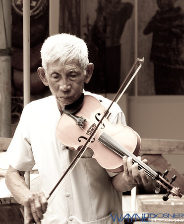 Elderly man playing for money at Chatuchak Weekend Market in Bangkok, Thailand.