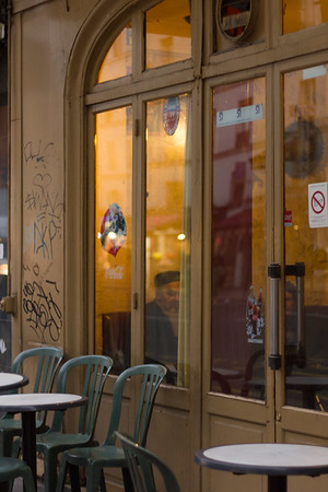 Peeking inside an old-style cafe with original zinc bar on Rue Faubourg-St Antoine, Paris.
