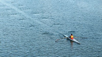 As he glides across the water in Seville, Spain, the canoer's oars leave a pattern in the water.