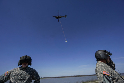 Air National Guard members wait for the all clear after attaching a sand bag to their helicopter Friday, March 9, 2018.
