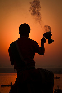A boy prepares morning offerings during sunrise on the Ganges River in Varanasi, India.