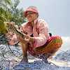 August 2, 2011 - A Koh Roung, Cambodia woman cleans the detritus out of Sihanoukville fishermen's nets on the village's beach. The dead animals that get caught in the nets, mostly crabs and starfish, are thrown into a nearby stream that, by the time it reaches the ocean, is dark with human and animal waste. The local dive shop and volunteers from Canadian organization Operation Groundswell constructed latrines in 2011 to help avoid tainting the drinking water with human excrement, but the village trash incinerator sits largely unused as heaps of garbage pile up around town. Photo/Christopher Weigl