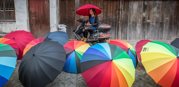An umbrella vendor stays dry with her own product in Suzhou, China.