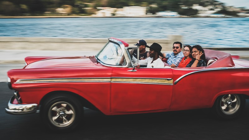 Local Cubans ride in a classic taxi car.