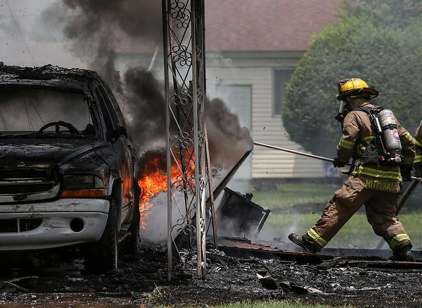 Arkansas Democrat-Gazette/MITCHELL PE MASILUN --6/17/2018--A North LIttle Rock Firefighter clears debris to better get to flames during a house fire on the 5000 block of Glenview Boulevard in North Little Rock Sunday, June 17, 2018. Initial reports stated that no one was in the house at the time and the cause is still under investigation. For more photos go to www.arkansasonline.com/Galleries