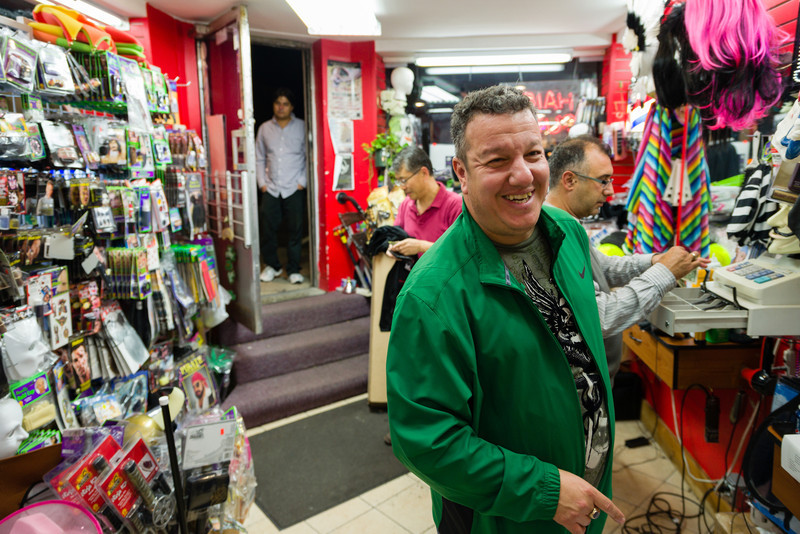"October 25, 2012 - Richard Lamoretti, the owner of Fast Eddie's Barber Shop on Harvard Ave in Allston, shares a laugh with a customer on Thursday night. Lamoretti constantly flits from customer to customer, cracking jokes and offering good deals under his breath. ""I love interacting with people,"" Lamoretti said. He estimated that 90 percent of the shop's haircut customers are regulars. Photo/Christopher Weigl"