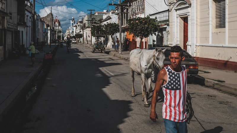 A Cuban wearing an American flag shirt walks a horse in the streets of Cienfuegos, Cuba.