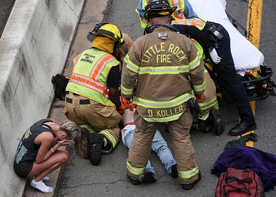 Little Rock Firefighters and paramedics attend to an injured person after responding to a multiple car accident on Eastbound I-30 near the 6th Street overpass in Little Rock Sunday, April 22, 2018.