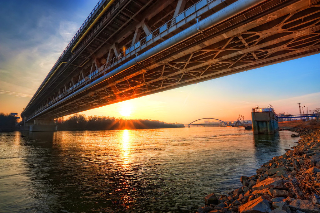Sun under the Port bridge  This is actually a very usual composition for me :) Having one bridge under another. But this time the sun gives it a special touch. This is the Port Bridge, one of the less accessible bridges in Bratislava, as it's a highway bridge, going over the cargo port.   This HDR is from 7 shots, as I vent as hight as +4 EV, because the bridge was very dark in every photo I took.   HDR from 7 shots, taken with Canon 450D with Sigma 10-20mm lens, from a tripod.
