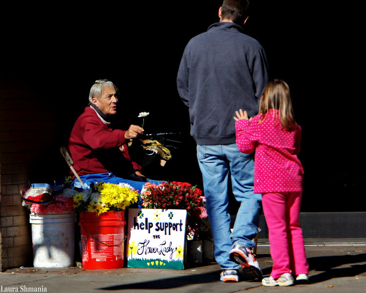 "11-8-09-- sunday chapel hill's ""flower lady"" lillie pratt offers a flower to a shy child.  lillie has been selling flowers on franklin street since the mid-50s.  the dad accepted the flower and tucked it behind his daughter's ear.  she then did a hop and a skip!   to read more about lillie, <a href =""http://dlatman.com/2007/10/17/lily-pratt-flower-lady/index.html"">click here</a>"