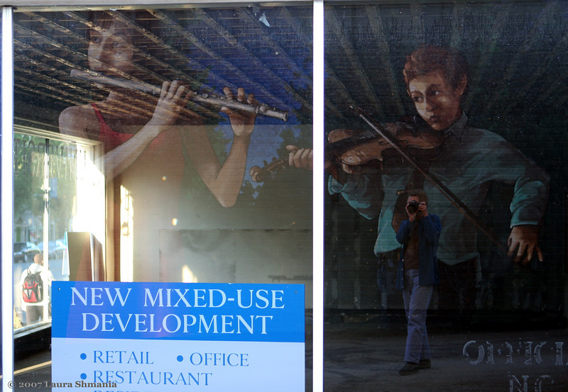 """10-14-07-- Sunday<br /> mural on the side of a building of musicians is reflected in the window of a vacant building-  along with me!<br /> <br /> chapel hill artist, michael brown, has painted 20+ large murals on the sides of buildings over the past 20+ years.  the ch preservation society has recently launched a campaign to preserve the murals.   <br /> <br /> my photo gallery of the murals is here:<br /> <br /> <a href=""""http://butterflites.smugmug.com/gallery/3647859#208338338"""">http://butterflites.smugmug.com/gallery/3647859#208338338</a>"""