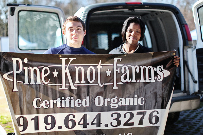 "The Carrboro Farmers' Market sits at the farthest west end of Franklin Street. While these two young'uns proudly displayed their farm's sign, the farmer's wife shared that her husband is a third generation farmer. ""It's all on the website,"" she said. Also on their website, ""The 2013 Farmer of the Year Award from the Carolina Farm Stewardship Association was presented to Stanley and Linda, who have an active program supporting youth as they prepare to become farmers and have given back to the community in numerous ways."" Congrats! Also found at the market: chicken eggs of all pastel colors, golden potatoes, and carrots with personality! <a href=""http://www.pineknotfarmsnc.com/"">http://www.pineknotfarmsnc.com/</a>"