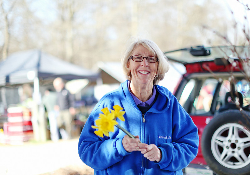 """Meet Carrie, owner of Fernrock Farm, so named because that's all that was on her land initially. She's always loved flowers and after retiring, she decided to """"drag a picnic table to the front of the road with cut flowers"""" and neighbors bought them! """"This might be fun!"""" Now she is six years into growing flowers commercially. She is especially passionate about dahlias and won nine blue ribbons at the most recent State Fair. Two interesting facts about daffodils: deer don't eat them and if you toss spent daffodils on the ground, they are apt to become bulbs and grow. At the Carrboro Farmers' Market"""