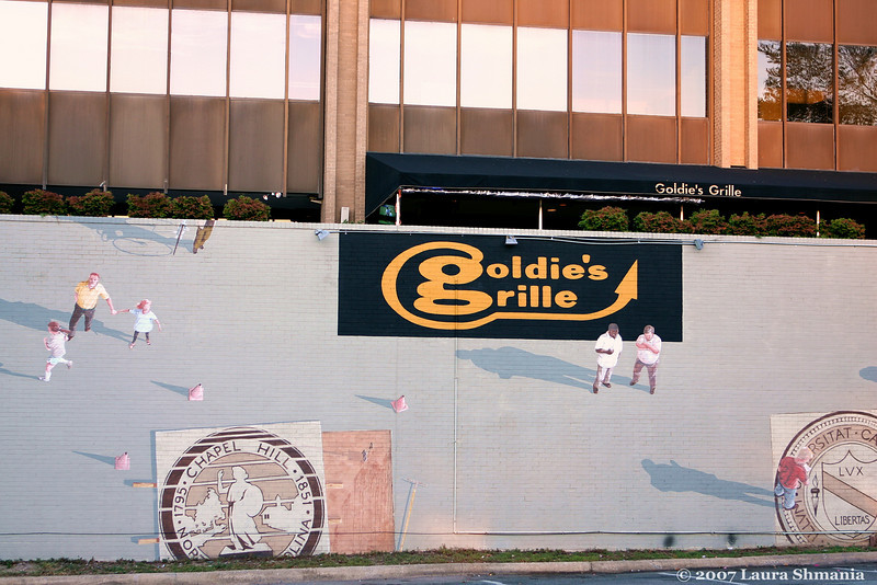 ARTIST'S STATEMENT- Goldie's Grill<br /> Public parking lot, corner of Rosemary and Columbia Streets<br /> <br /> This mural depicts downtown pedestrians viewed from above. It creates the illusion that the viewer is looking down or that the pedestrians are walking up a wall. I was inspired by all the trouble and protest we had in town when N. C. N. B. first proposed this building. The idea of a 6 storey building on Franklin Street drove people right up the wall. Citizens even floated balloons to that height so folks could get a feel for how tall the building would be. It is of course on that building that the mural was painted in 1996.<br /> The head of the Downtown Commission, Robert Humphries, was having a hard time finding a building owner to lend us a wall for that spring. I try to make the murals site specific but since we had no site, I had no idea and no proposal sketch. Without those things Robert was having a hard time getting donations, too. The mural was supposed to be the centerpiece of a local arts festival and our deadlines were looming. He finally got a building, but only a week before the festival. With no time to spare Robert and I had to cut through a lot of red tape to get the mural started on time. The main benefit of such a mural, with it's flexible composition, was that I could paint while Robert did fundraising, Every time he got a donation I added more people to the mural.