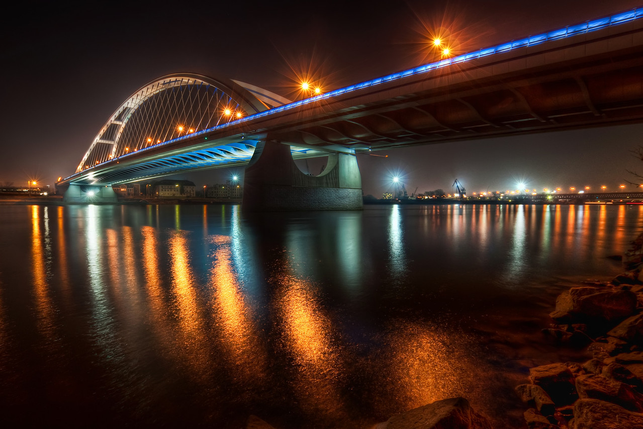 Apollo Bridge Lights  I just love taking photos of bridges. I return to the ones in Bratislava quite often, always trying to get a better shot :). So here is another one of the Apollo bridge, taken about an hour after the sunset. You can see the Bratislava port behind the bridge.  HDR from three shots, taken with Canon 450D with Sigma 10-20mm lens, from a tripod.