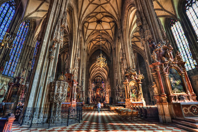 Man vs. Cathedral  I haven't noticed the man in the middle until I processed this photo. It almost looks like he is posing there :). It gives the photo a really nice sense of scale, comparing him to the the size of the cathedral. This photo was taken in the St. Stephen's Cathedral in Vienna.  HDR from three shots, taken with Canon 450D with Sigma 10-20mm lens, handheld.