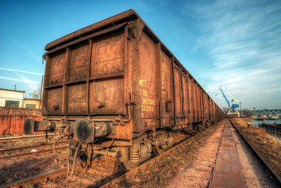 Wagons in the harbor  Train can give you such a nice vanishing point, the longer the better :). This photo was taken earlier this year in the Bratislava harbor. The sun was already quite low, and behind me, so if you look closely you can see the shadow of the camera.   HDR from three shota, taken with Canon 450D with Sigma 10-20mm lens, from a tripod.