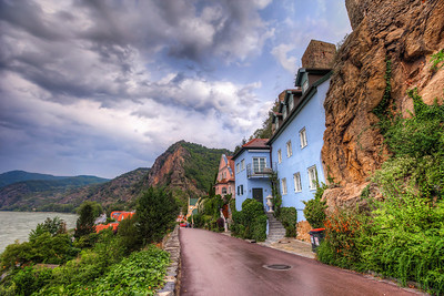 Houses in the hill It looks interesting, when they build houses directly into a hill. Even if the houses are quite new, it still looks kind of medieval :) I took this photo in Durnstein, in Austria. It was raining a little, so that's why a really cloudy sky and a shiny road.