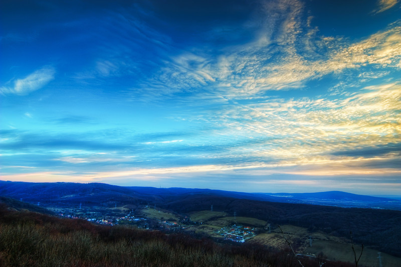 Blue Sunset  This photo was taken from the Pajstun castle ruins in Slovakia, around sunset. It was actually quite strange, how blue the sky was. Usually when I take sunset photos I get a lot of shades from pink to purple, but this sunset, it was just shades of blue. And all other photos taken around this time are also very blue :). I tried to play with the temperature of this photo, to make it a little warmer, but then I lost the beautiful shades of blue in the so I let it be.  HDR from three shots, taken with Canon 450D with Sigma 10-20mm lens, from a tripod.