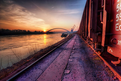 Long train running  I took a little walk through the cargo port in Bratislava last weekend and I took a lot of shots :). As is visible on the photo, this was taken right at the sunset, which gave such nice colors to the photo. You can see the Apollo bridge in the distance with one of the port cranes.  Btw. the title was inspired by the Doobie Brothers song :)  HDR from three shots, taken with Canon 450D with Sigma 10-20mm lens, from a tripod.