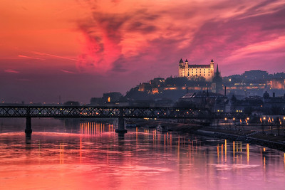 Burning Sunset  A little different view of the Bratislava Castle. I took this photo from the Apollo Bridge. I wasn't really sure, if a longer exposure will work, as the bridge is shaking a little from the passing cars, but it had no visible effect.  HDR from three shots, taken with Canon 450D with Sigma 18-200mm lens, from a tripod.
