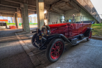 Parked  At first I didn't like this photo. I took it only because of the car, and I thought the background doesn't fit here at all. But after I edited it in photomatix, I started to like it. The contrast between the beautiful old car and the ugly concrete pillars worked out actually quite well.   I took here exposures from -4EV to +2EV, but it still wast enough to have a blue sky in the shot :)  HDR from 4 shots, taken with Canon 450D with Sigma 10-20mm lens, from a tripod.