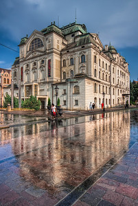 Still raining  I had to be very careful taking this photo. My camera is not weatherproof, so I had to be careful not to get it too much into the rain :) I'ts also nice to be able to get a reflection somewhere, where usually there is no reflection. This photo was taken in the center of Kosice, this is the State Theater.  HDR from three shots, taken with Canon 450D with Sigma 10-20mm lens, handheld.