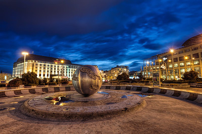 Hodza Square  One more blue hour shot from center of Bratislava. I actually went inside the fountain, to take few show with reflections from the water puddles :)  HDR from three shots, taken with Canon 450D with Sigma 10-20mm lens, from a tripod.