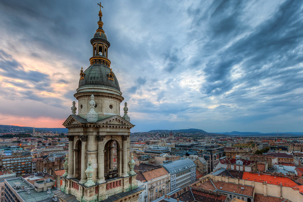 Sunset above Budapest This one was taken from the top of the St. Stephens basilica in Budapest, during one very cold sunset. I had to hold the camera most of the time, as it was too light to stand still in the heavy wind. The sunset was a little more colorless than I hoped, so I thought it will be better during the blue hour. But as the tower has very strong flood lights, once those were one, no further shooting was possible.