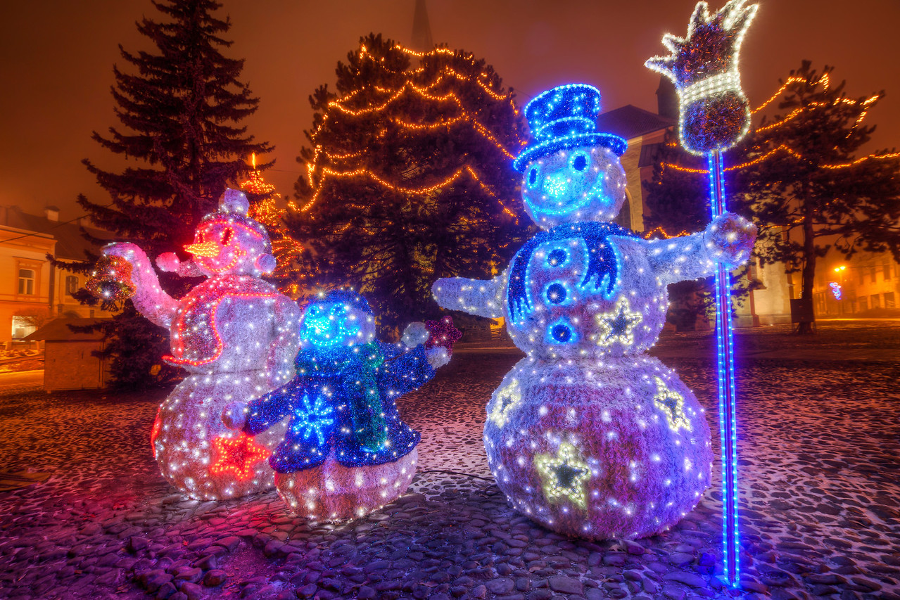 Snowman family  I had no Christmas photos before Christmas, but I have some now :). This are part of the Christmas decoration in the city Presov. I took this quite late at night. I was hoping for a nice photo overlooking the city, but as you can see in the background, there was a really heavy fog that night.  HDR from three shots, taken with Canon 450D with Sigma 10-20mm, from a tripod.