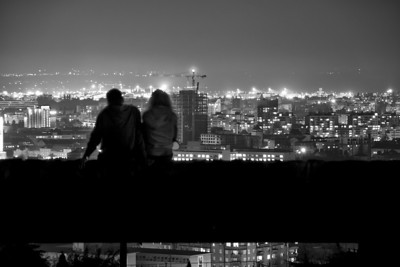 Date in the Light sea  I went up to the Slavin memorial above Bratislava, to take few night shots of the city, when I saw this young couple, sitting on one of the walls. I couldn't resist to take this shot. I really love how it turned out, I think the composition worked out great :)  Single photo, converted into B&W using Silver Effects. Taken with Canon 7D with Sigma 18-200mm lens, from a tripod.