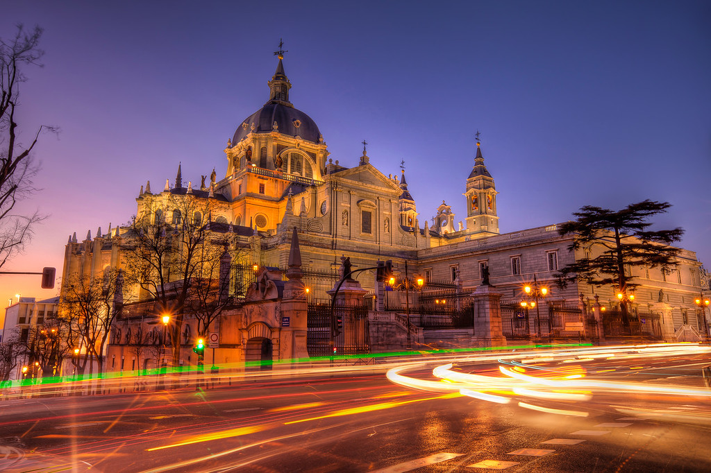 Sunset by the Almudena CathedralWould be nice to take this photo without cars, but that was really not possible. So instead I went for light trails. I took the same shot few times, until I had a photo, where none of the cars was visible. I also played a lot with the colors on this one, but in the end I chosen a little warmer look. I really like it :)HDR from three shots, taken with Canon 5D mark II with Canon 16-35mm F2.8 lens, from a tripod.