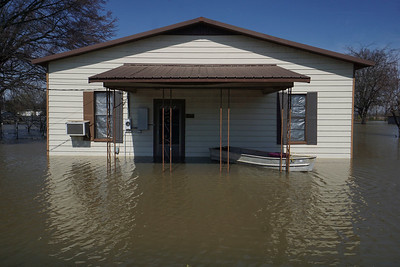 A house sits submerged as a boat sits nearby ready to be used in Homnoke Friday, March 9, 2018. Humnoke, a town of fewer than 300 people, sits at the intersection of Arkansas 13 and U.S. 165 in the southeast corner of the county and has a lower elevation than the communities around it