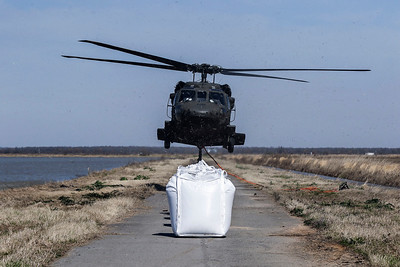 An Arkansas Air National Guard helicopter takes off Friday, March 9, 2018. Each bag is white, about 4.5 feet wide and 5 to 6 feet in length, weighs 4,000 pounds and has handles