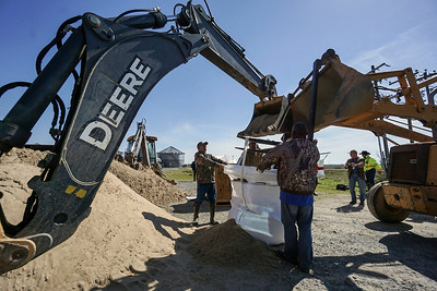 Crews used a backhoe to fill sandbags, which will be used to plug up the Levee, just north of Homnoke Friday, March 9, 2018.