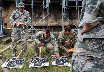Competitors cross judge each others' targets after a round during the Winston P. WIlson Championship Armed Forces Skill at Arms Meeting at Camp Robinson Thursday, May 3, 2016