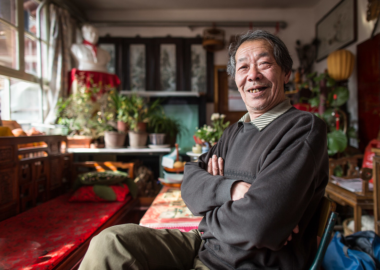 Mr. Liu, a Prize-Winning Cricket Fighter, poses for a portrait in his home in Beijing.