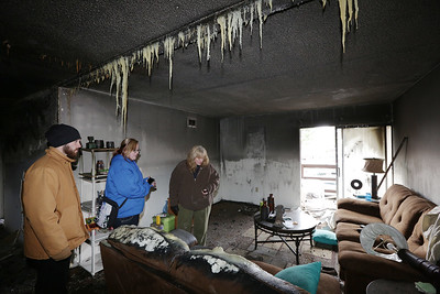 David Dashkovitc, Casey Miller, and Catre Miller assess the damage after a fire destroyed their apartment at 750 Maple Street