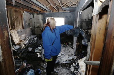 Casey Miller sifts through debris after a fire destroyed her apartment at 750 Maple Street