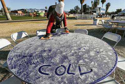 Makenzie Stine, am Arizona Bowl intern, wipes frost off tables before tailgaters arrive on the Midway before the start of the Arizona Bowl Satuday, Dec 29, 2018 in Tucson, Arizona.