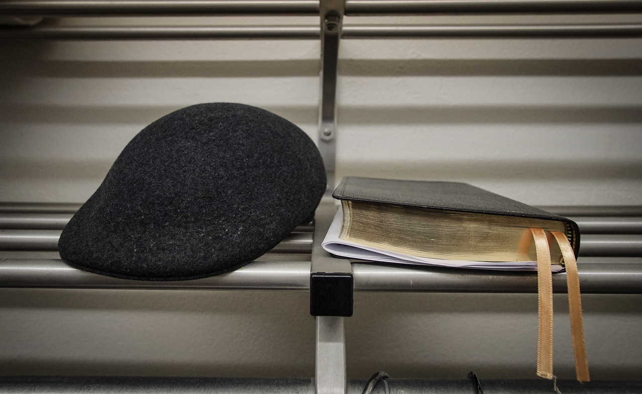 A hat and bible lie in a closet.