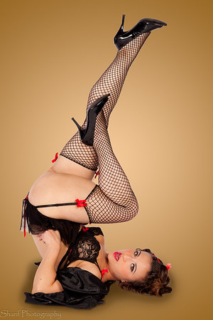 A young woman in lingerie poses in the classic legs-up pin-up pose.