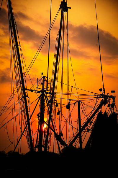 Working shrimp boat silhouetted against a sunset sky at Shem Creek, South Carolina.
