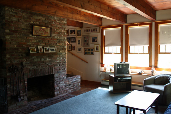 """Living room, stairs to the second floor are to the right of the fireplace. This TV has been replaced with a 32"""" HD flat screen."""
