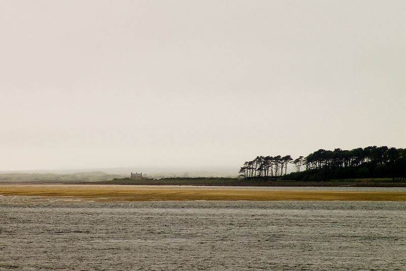 A solitary house during a dreary day, taken on the 1st of June, 2005. The beach can be seen in the mist from Canerfon, North Wales. A panoramic crop is also availabile